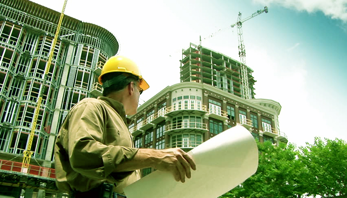 An Architect observes the large building with a plan on his hand.
